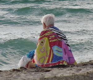 senior sitting at the beach