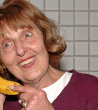 senior woman using banana as telephone