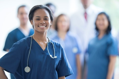 A nurse is happily standing in front of her colleagues at the hospital. She is wearing her scrubs and is miling while looking at the camera.